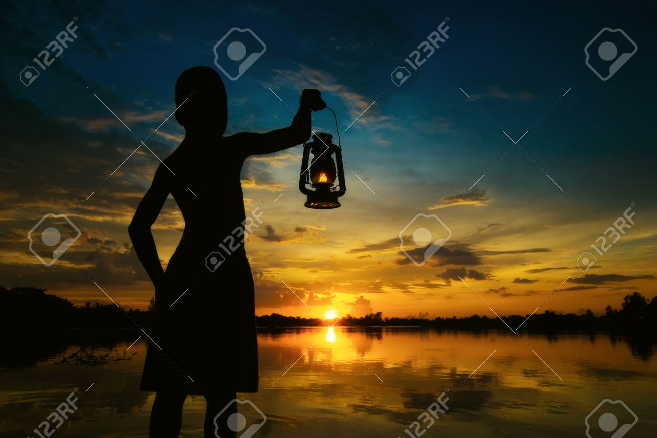 Boy Holding Lamp Looking For Sunset . Abstract Meaning Hope Of Life. Stock  Photo