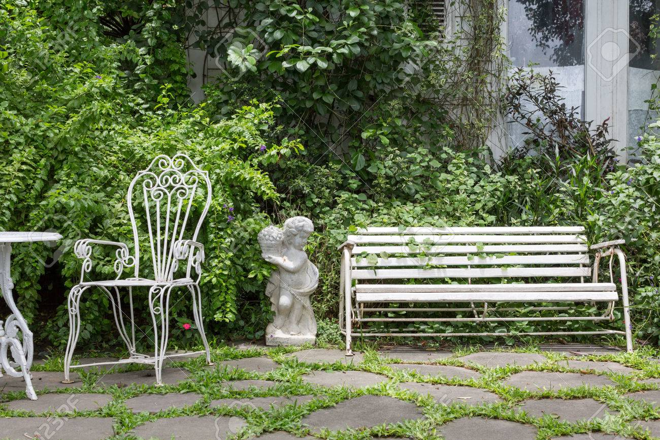 White Alloy Bench In Outdoor Garden With Vine Covered White House ...