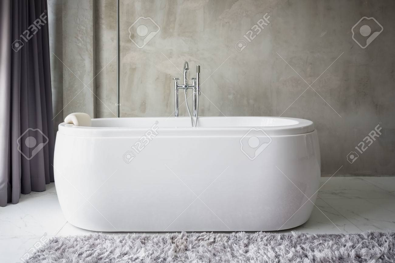 Big White Bathtub In A Middle Of Minimalist Bathroom With Grunge Cement  Wall. Stock Photo