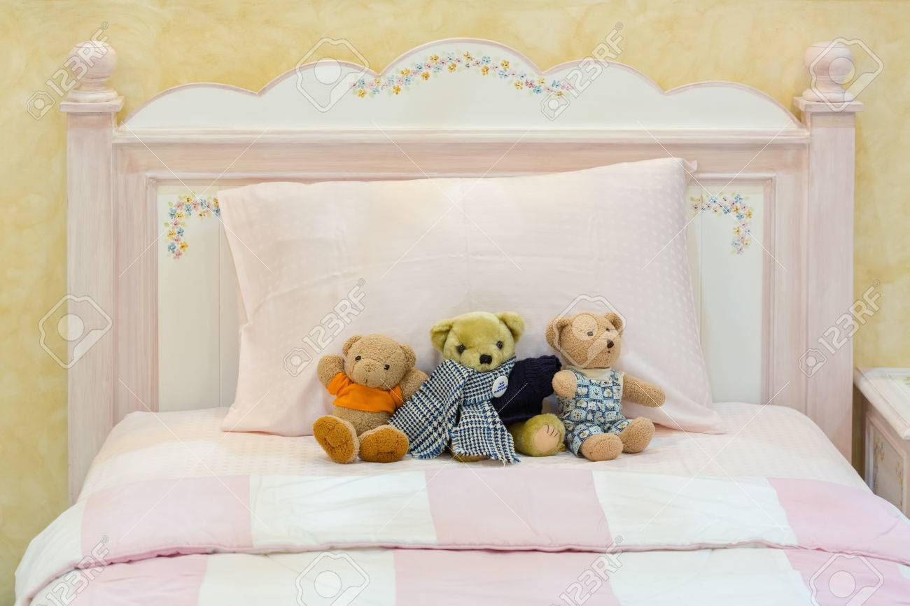 Teddy bears on a pink bed and pillows in old English country..