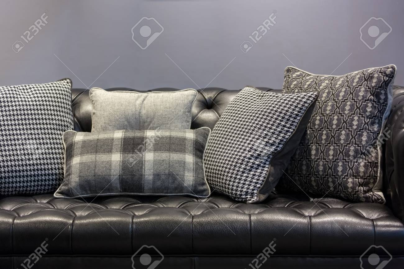 Vintage Style Black Leather Sofa And Pillows In A Gray Living