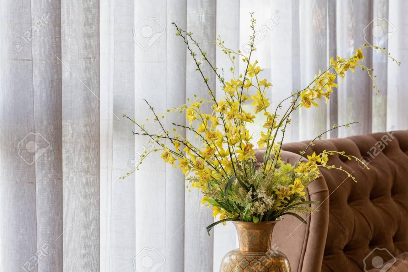 Standard Bild   Wilde Gelbe Orchidee In Einem Keramischen Vase Verziert  Nahe Einem Sofa Und Einem Weißen Vorhang.