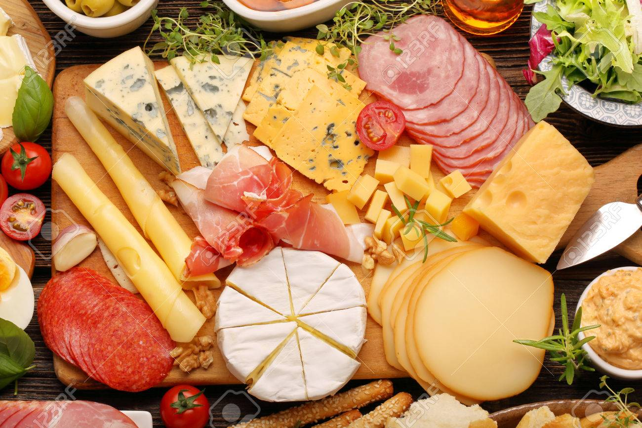 Buffet Of Various Types Cheese And Appetizers Set On Rustic Wooden Board Stock Photo