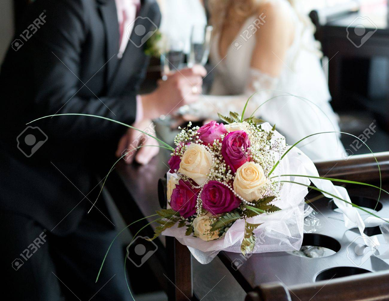 a bridal bouquet of roses, in the background - a groom and a bride hold wine glasses Stock Photo - 12816465