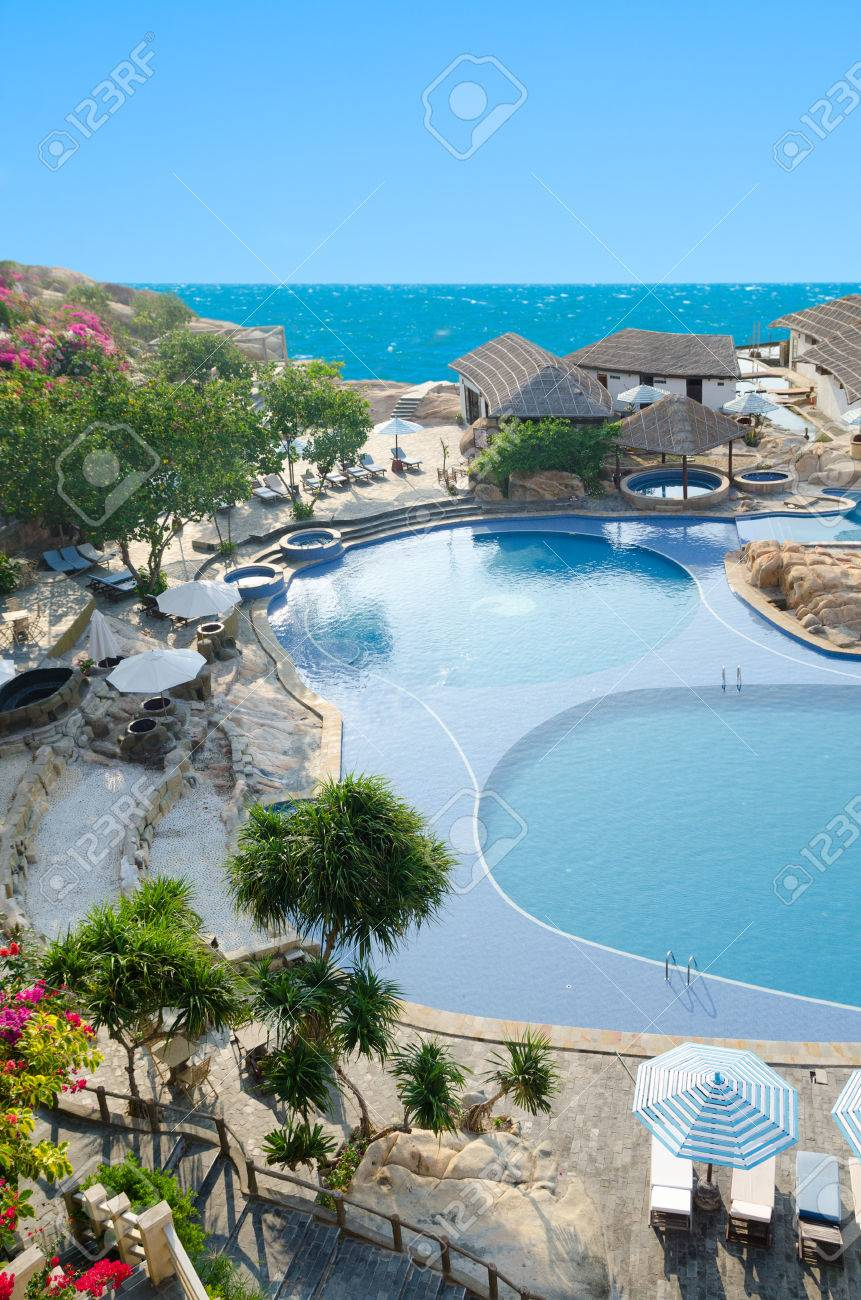 swimming pool with sunshades and sunloungers near hotel