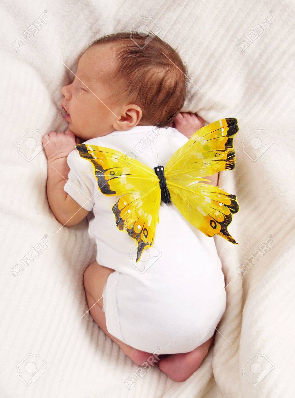 Sleeping child with the butterfly on a back on a light blanket. Stock Photo - 6180997