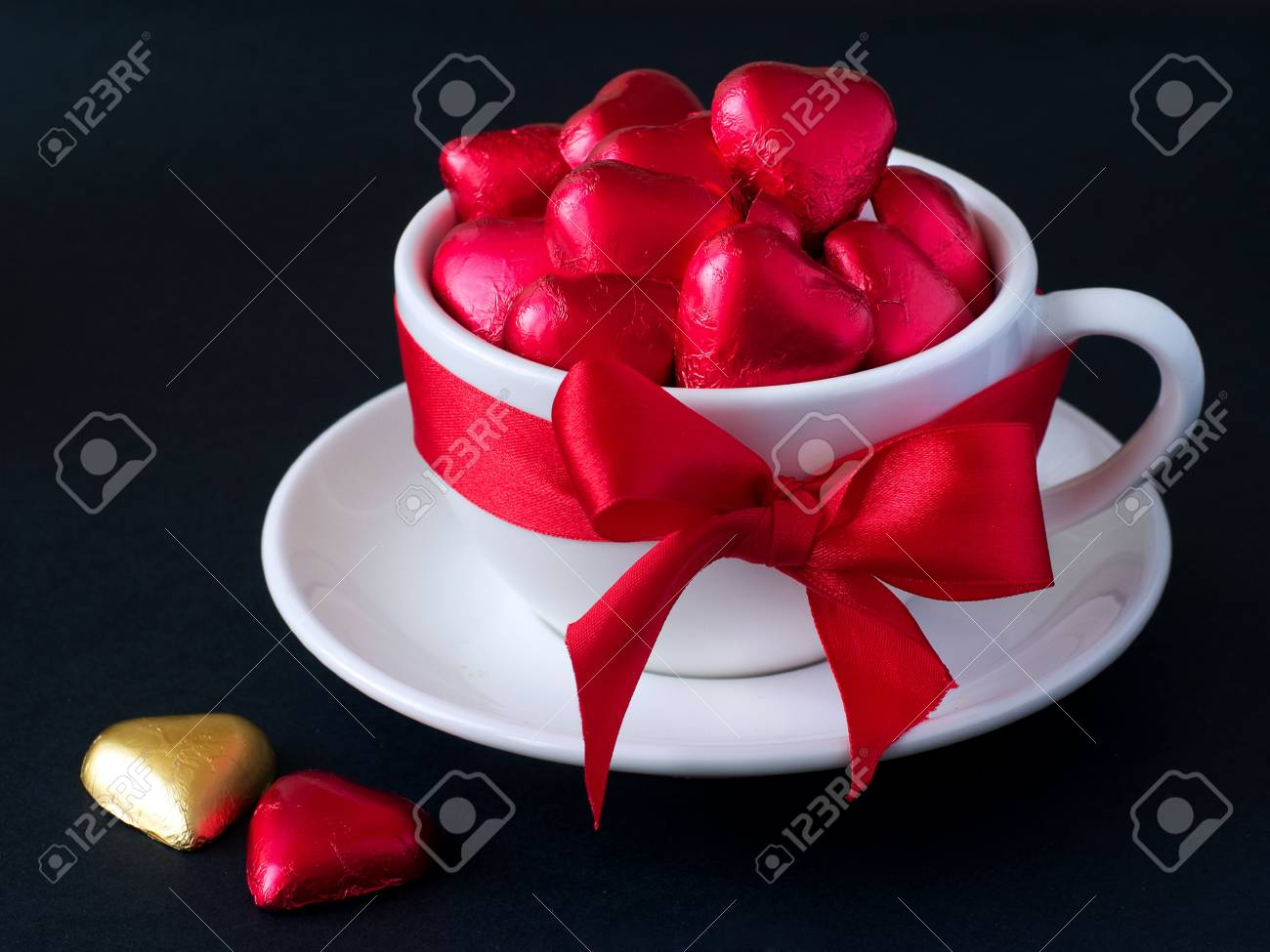 White cup with saucer with red and gold chocolate hearts and red ribbon. Photo on a black background Stock Photo - 6204290