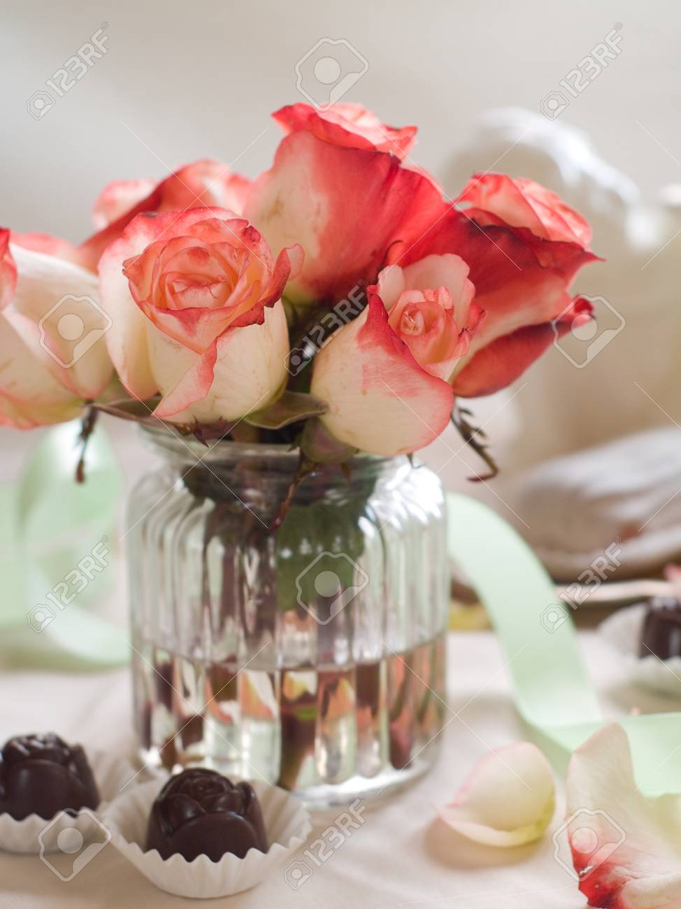 Beautiful Roses In Glass Vase With Chocolate Candy For Celebration