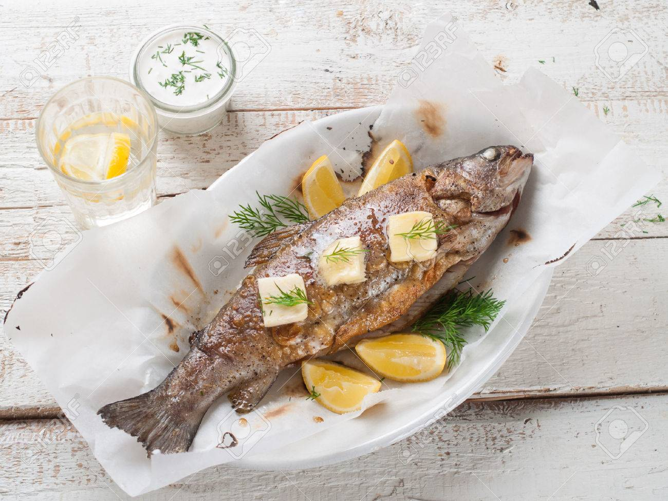Grilled fish with butter and lemon, selective focus - 39016754