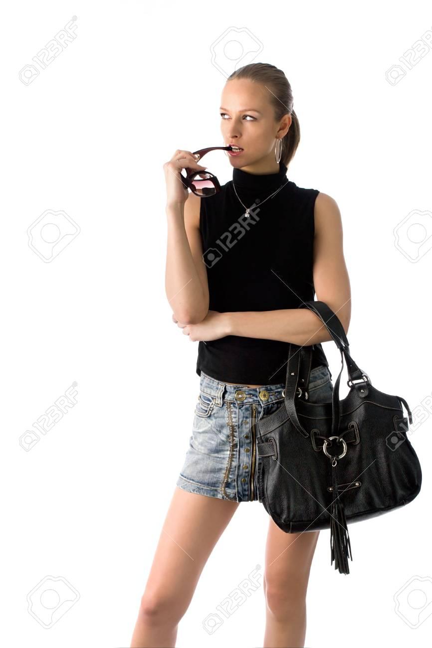 bb5cb022eeaf88 Banque d images - Belle jeune femme en noir t-shirt, jupe courte et des  lunettes de soleil, avec sac à main en cuir noir, isolé sur blanc