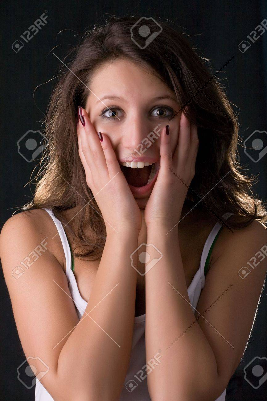 beautiful young girl with happy surprised smile isolated on black Stock Photo - 2549908