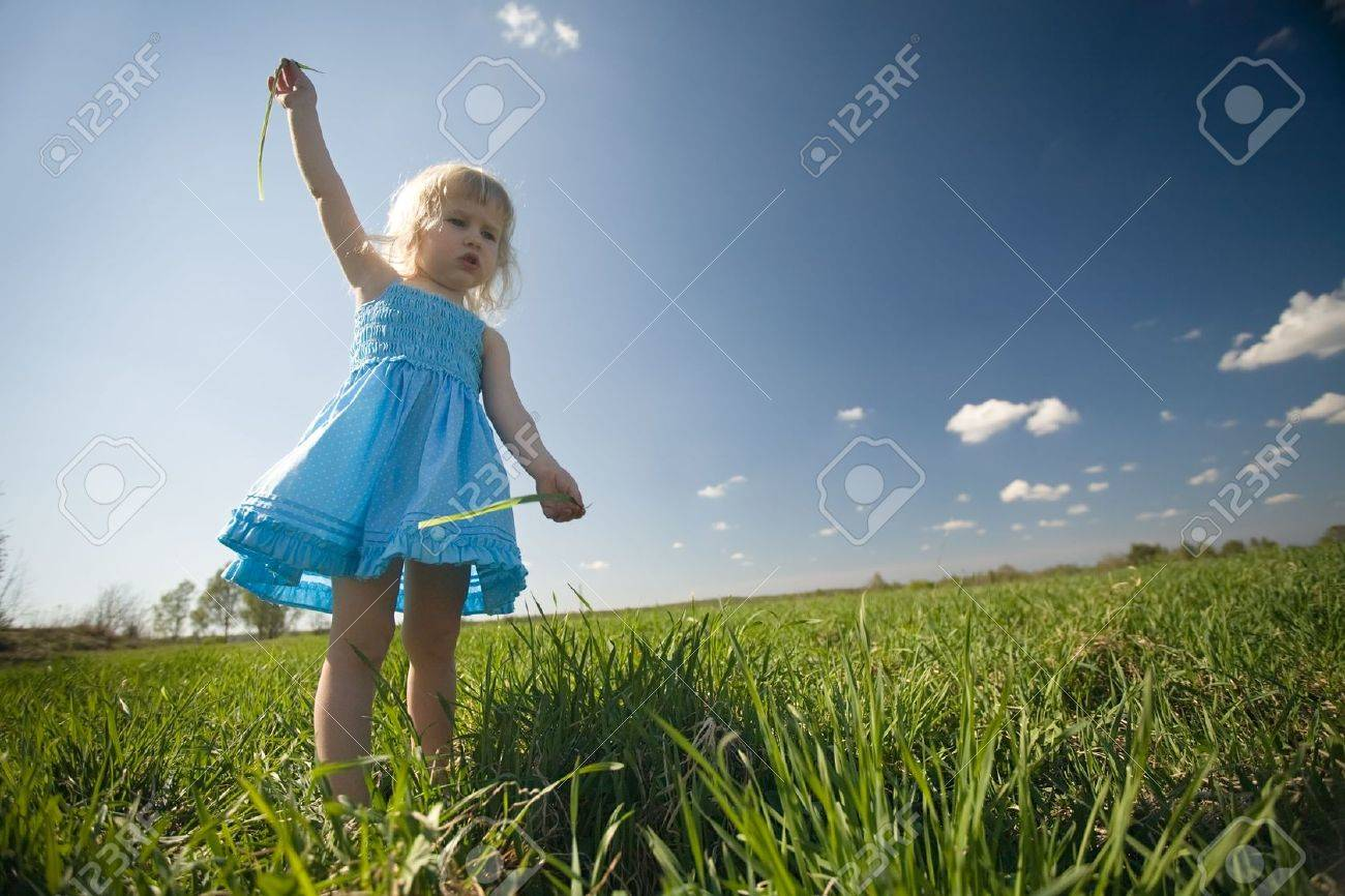 funny little girl in blue dress on green meadow and blue sky background Stock Photo - 3058424