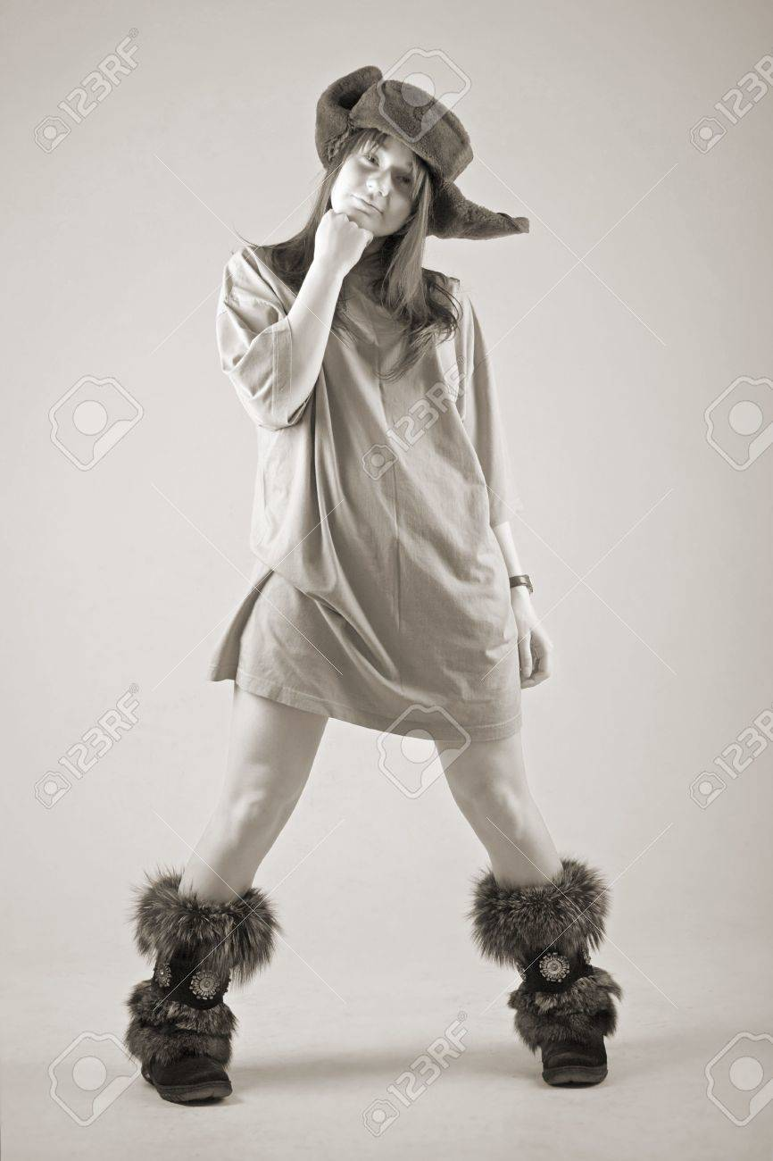 funny young woman in russian earflapped fur hat and fur boots