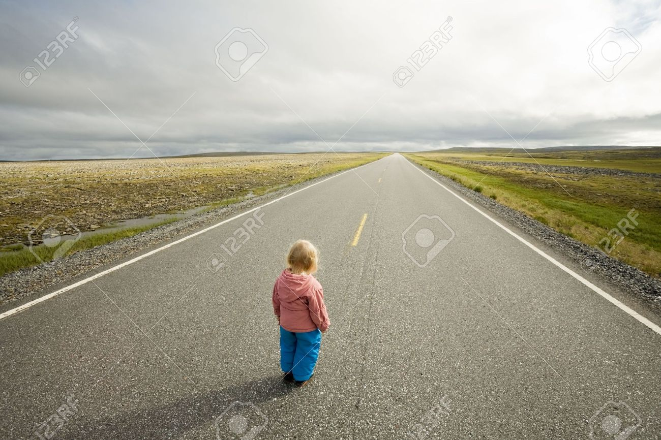 little child standing at the beginning of straight road going to horizon Stock Photo - 3503625