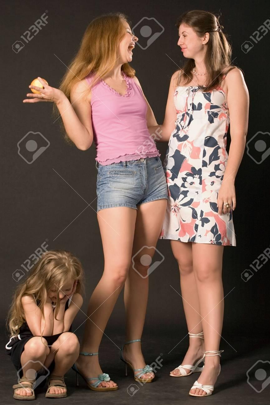 dos mujeres jóvenes conversando con sonrisas y triste niña sentada cerca sobre fondo negro  Foto de archivo - 3599330