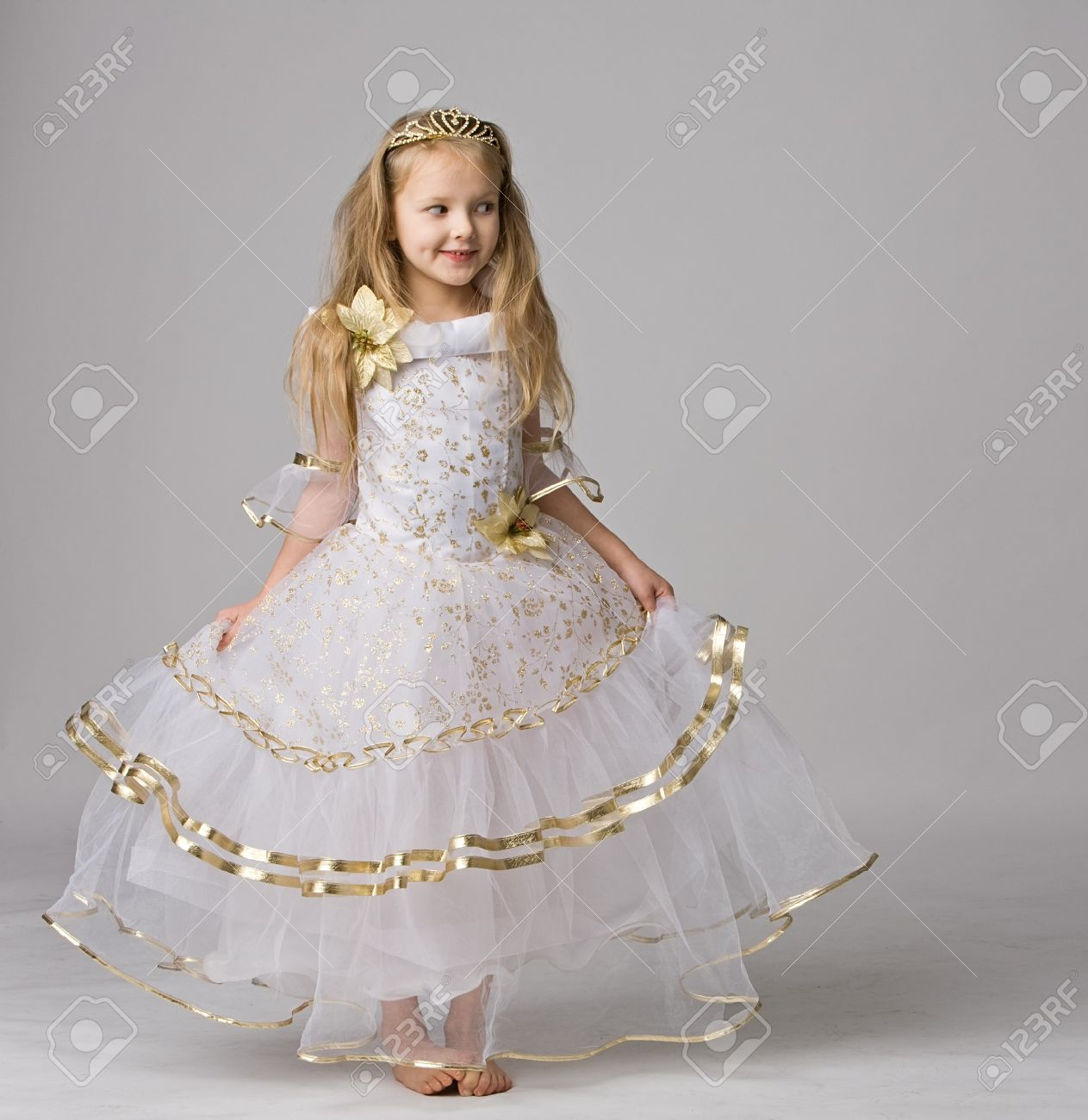 beautiful little girl in dress of princess with diadem on long hair barefoot  stand isolated on
