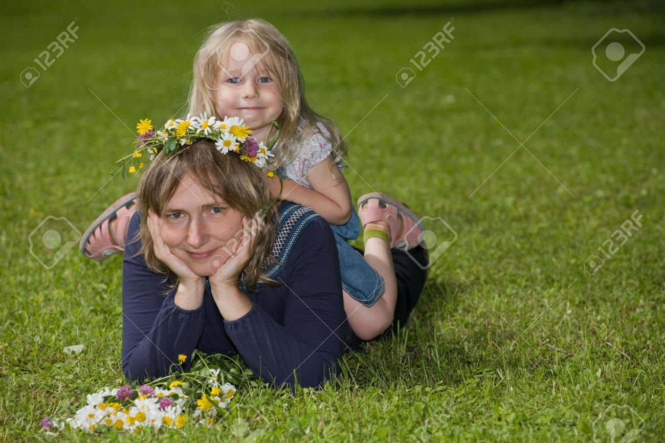 portrait of a mother lying on the lawn with her daughter sitting on her back, in the outdoors Stock Photo - 5578872
