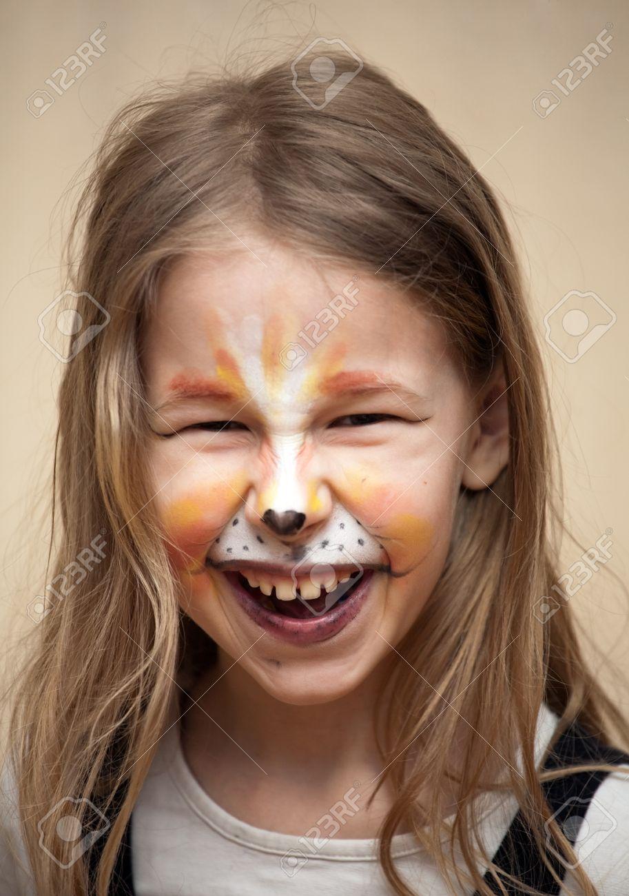 Banque dimages , closeup portrait dune petite fille avec la peinture de chat de maquillage sur le visage en regardant la caméra