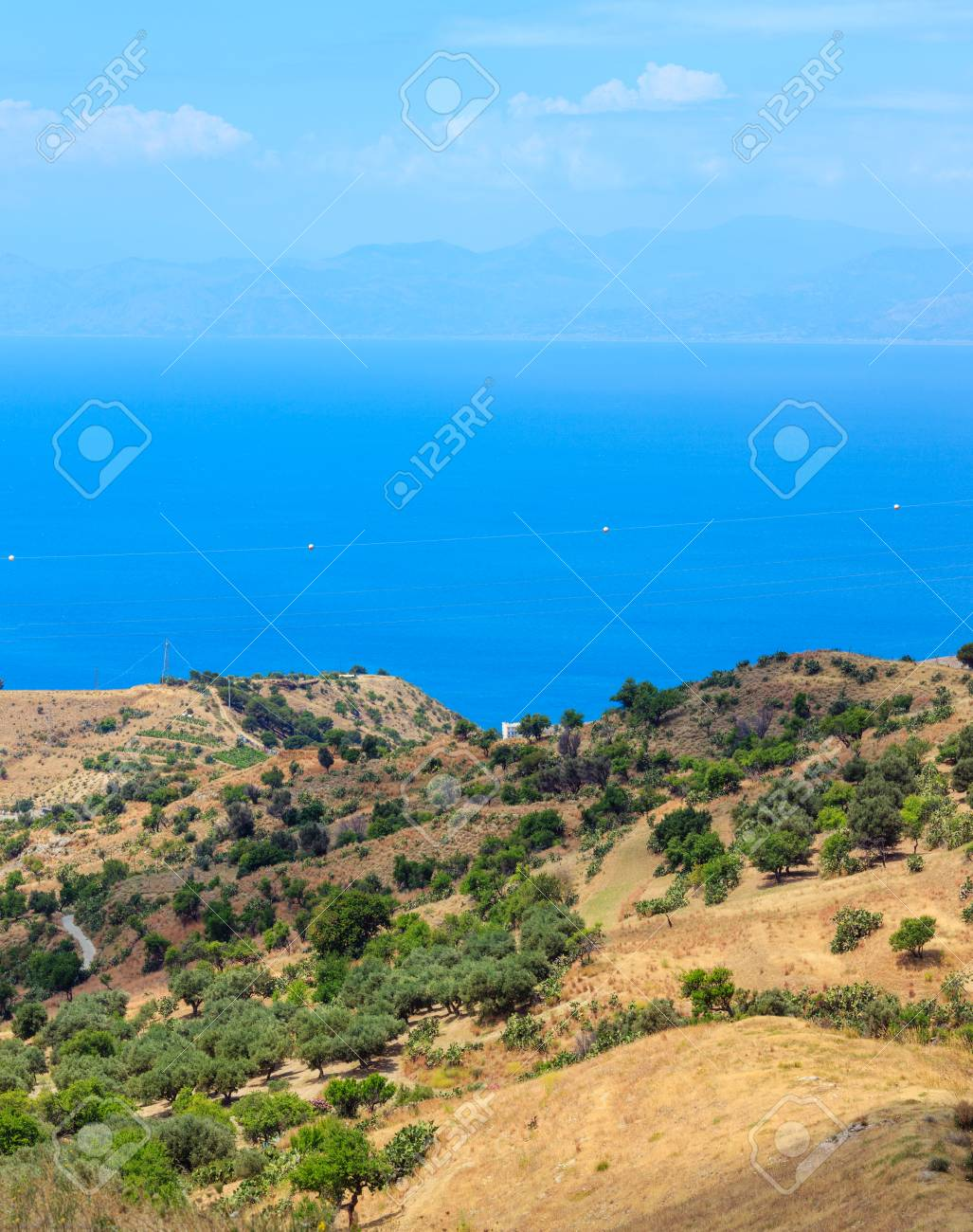 Picturesque summer view to sea and Sicily island in far from mountain hills in Motta San Giovanni outskirts, Reggio Calabria, Italy. - 104571867