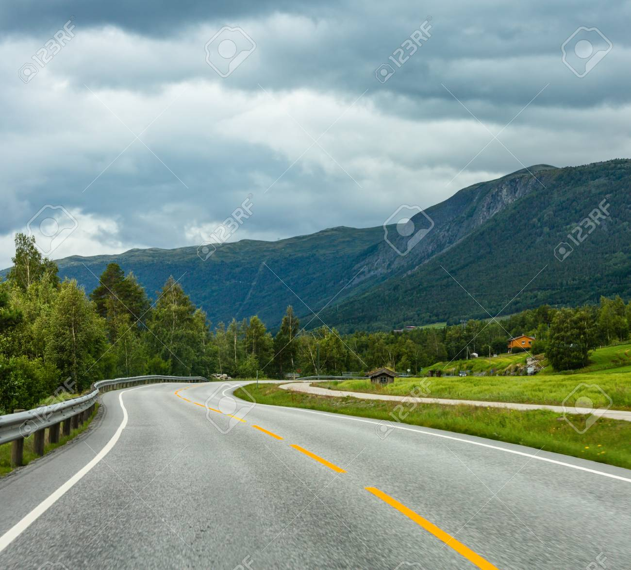 Summer cloudy mountain landscape with serpentine secondary road, Norway - 120986414