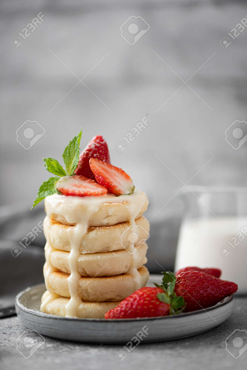 cottage cheese pancakes with fresh strawberries, mint and milk on a gray plate - 155546499