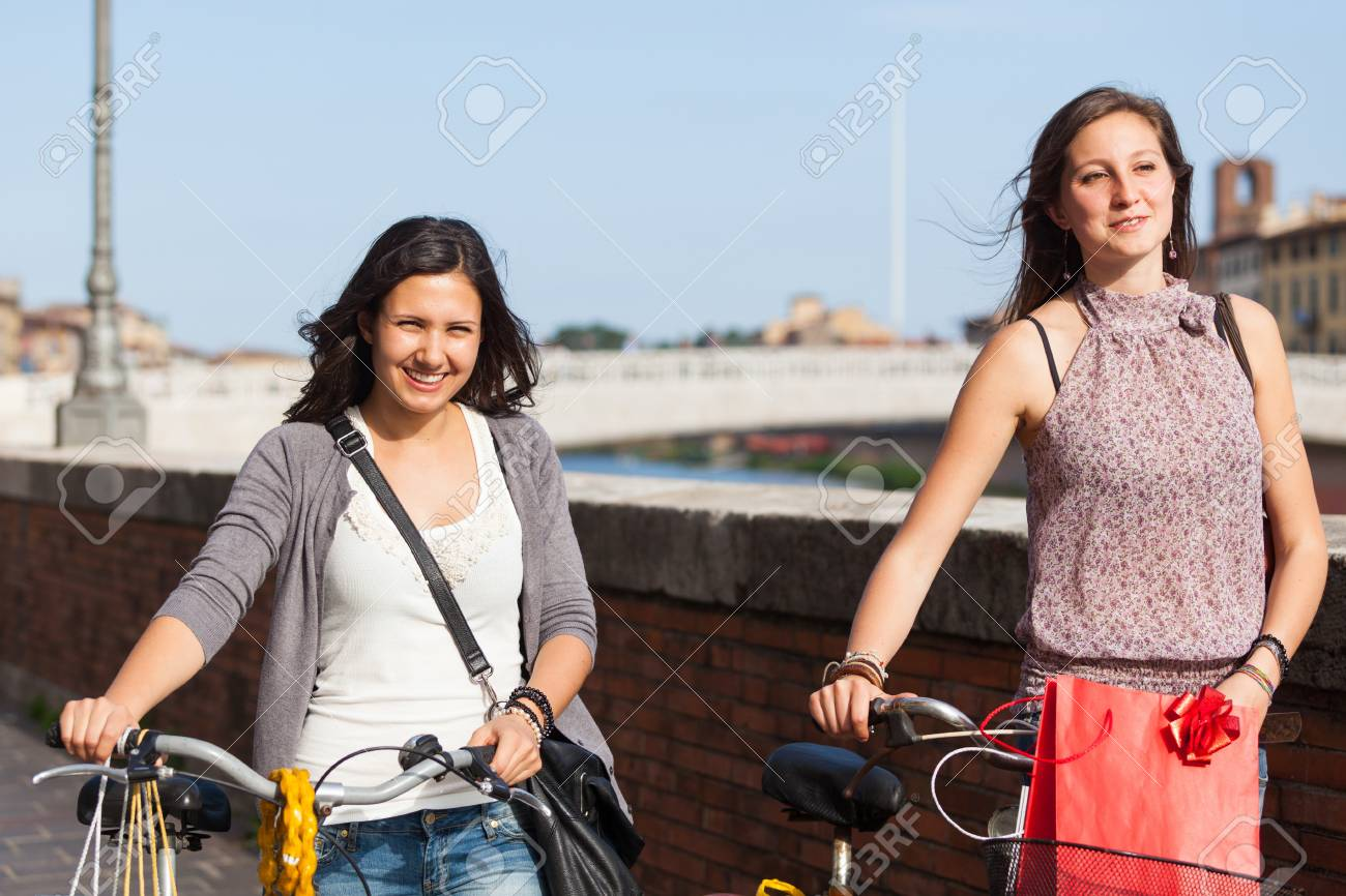 Two Beautiful Women Walking in the City with Bicycles and Bags Stock Photo - 17469380