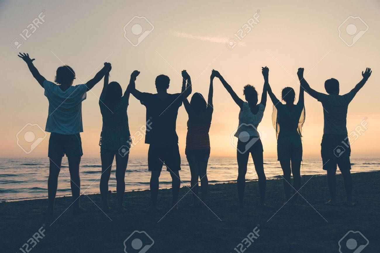 Group of People with Raised Arms looking at Sunset Stock Photo - 25641896