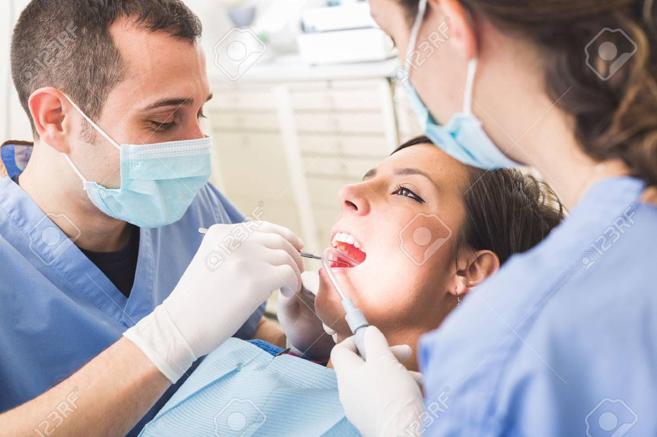 Dentist And Dental Assistant Examining Patient Teeth Is A Man
