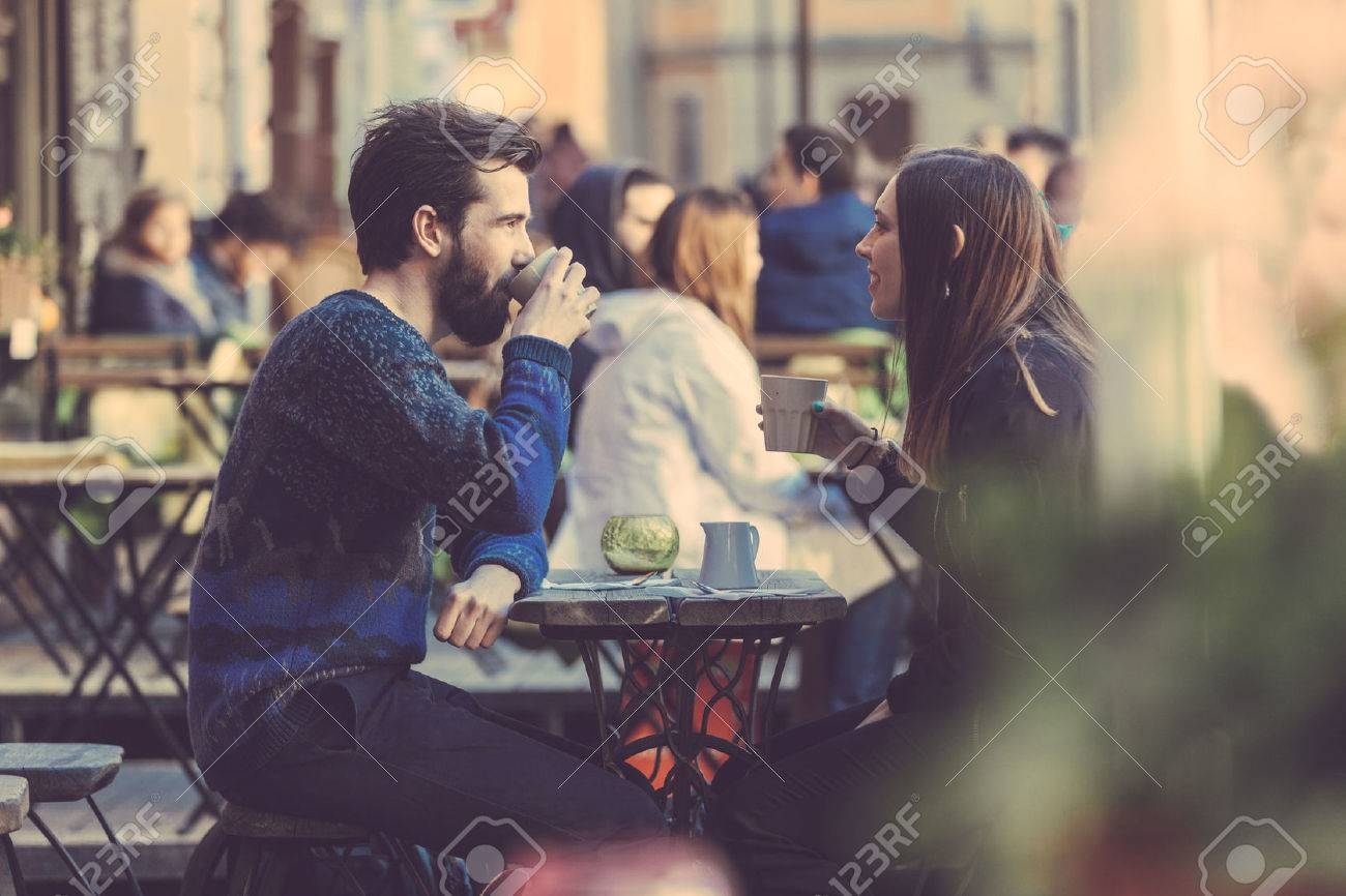 Hipster couple drinking coffee in Stockholm old town. They're sitting face to face. The man is wearing a blue sweater and the woman a striped shirt with black leather jacket. See-through shot. Stock Photo - 39800621
