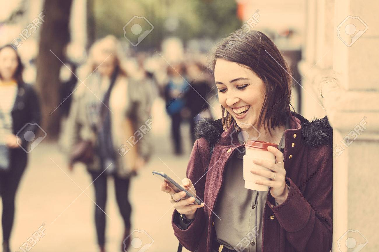 Young woman in London standing by the sidewalk, holding a cup of tea and typing on her smart phone. It is a cloudy winter day, and there are many blurred persons on background. Stock Photo - 47372828