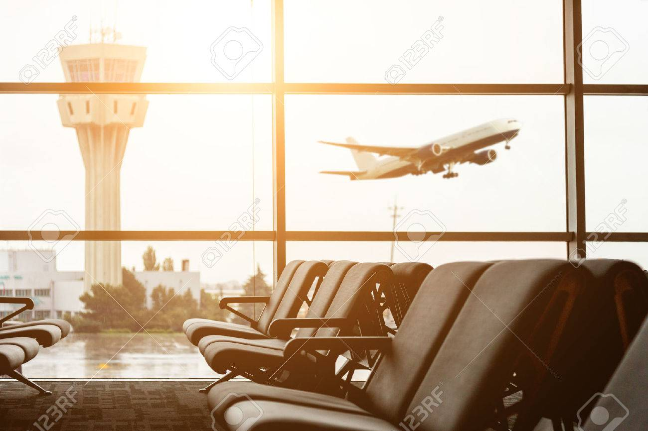 Empty chairs in the departure hall at airport , with the control tower and an airplane taking off at sunset. Travel and transportation concepts. - 50964379