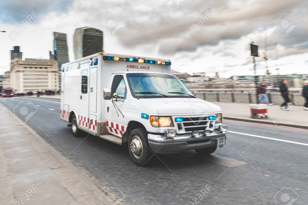 Emergency ambulance rushing on the street with emergency lights emergency ambulance rushing on the street with emergency lights flashing in london city centre medical mozeypictures Choice Image