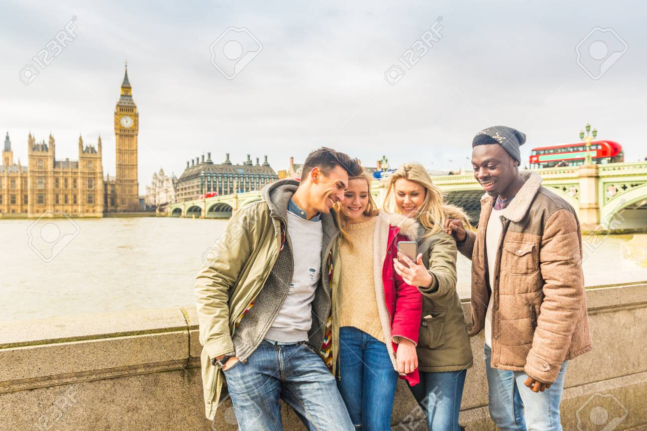 Happy multiracial friends group using smartphone in London. Mixed race millennials people lifestyle concept. Friends sharing trip on social network. Big ben and Westminster parliament on background. - 120028795