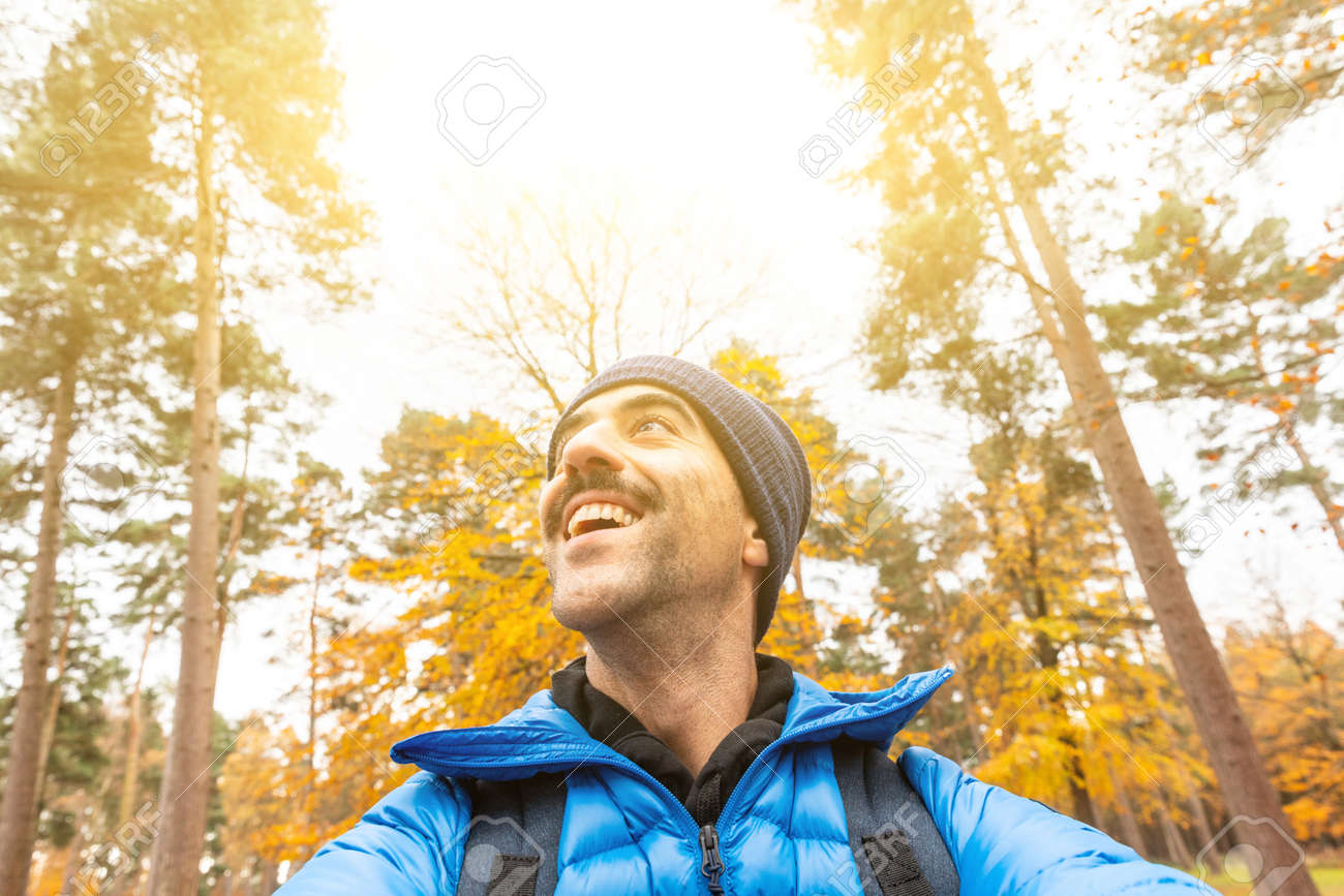 Happy man taking a selfie in the wood with beautiful autumn vibes - Young man alone enjoying time in a remote forest away from city and busy life - lifestyle and nature - 158569076