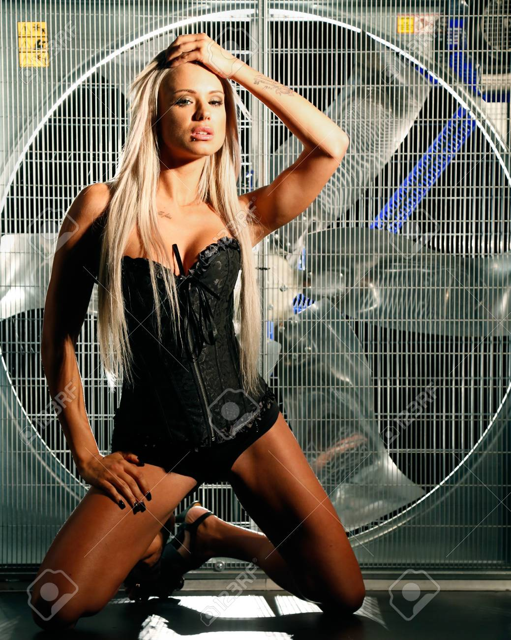 very sexy and beautiful woman is posing with a huge industrial turbo wind fan behind her were smoke and lights are coming trough Stock Photo - 15448361