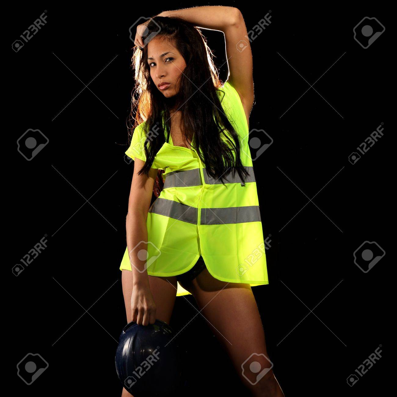 Very beautiful and sexy working woman wearing a safety or security jacket or vest and a helmet Stock Photo - 16968866