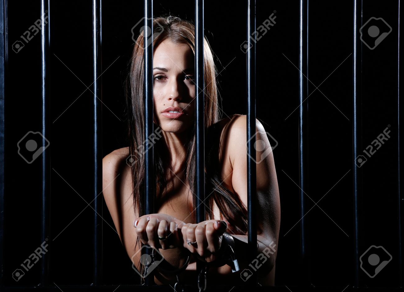very sexy and beautiful nude woman locked behind black prison