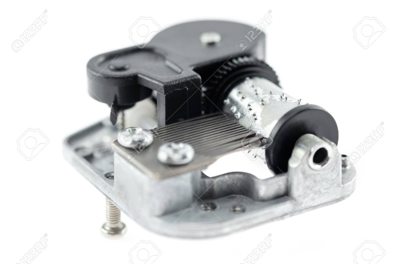 Music box melody mechanism on white background  Shallow depth