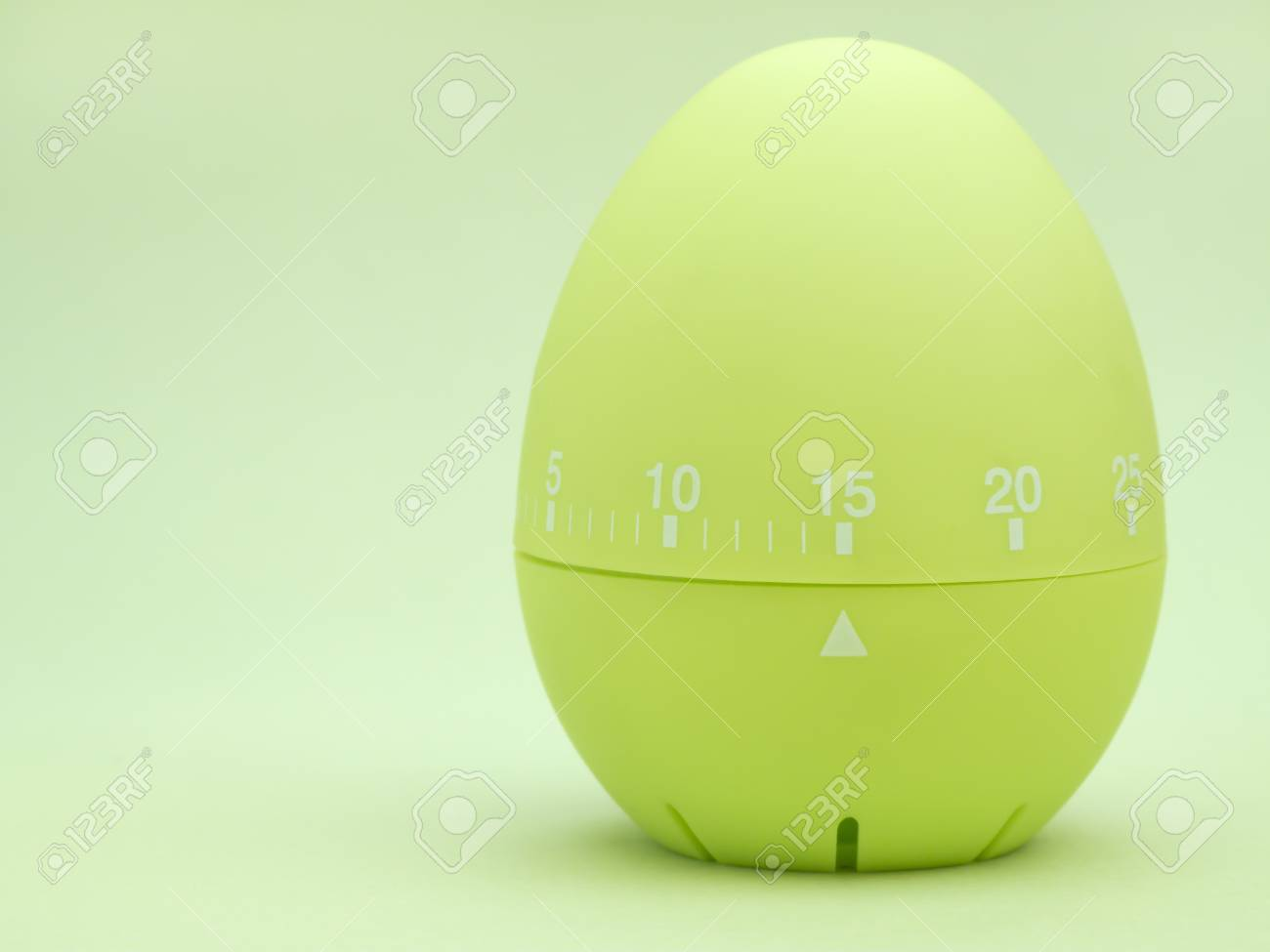 green egg shaped kitchen timer set to 15 minutes on green background