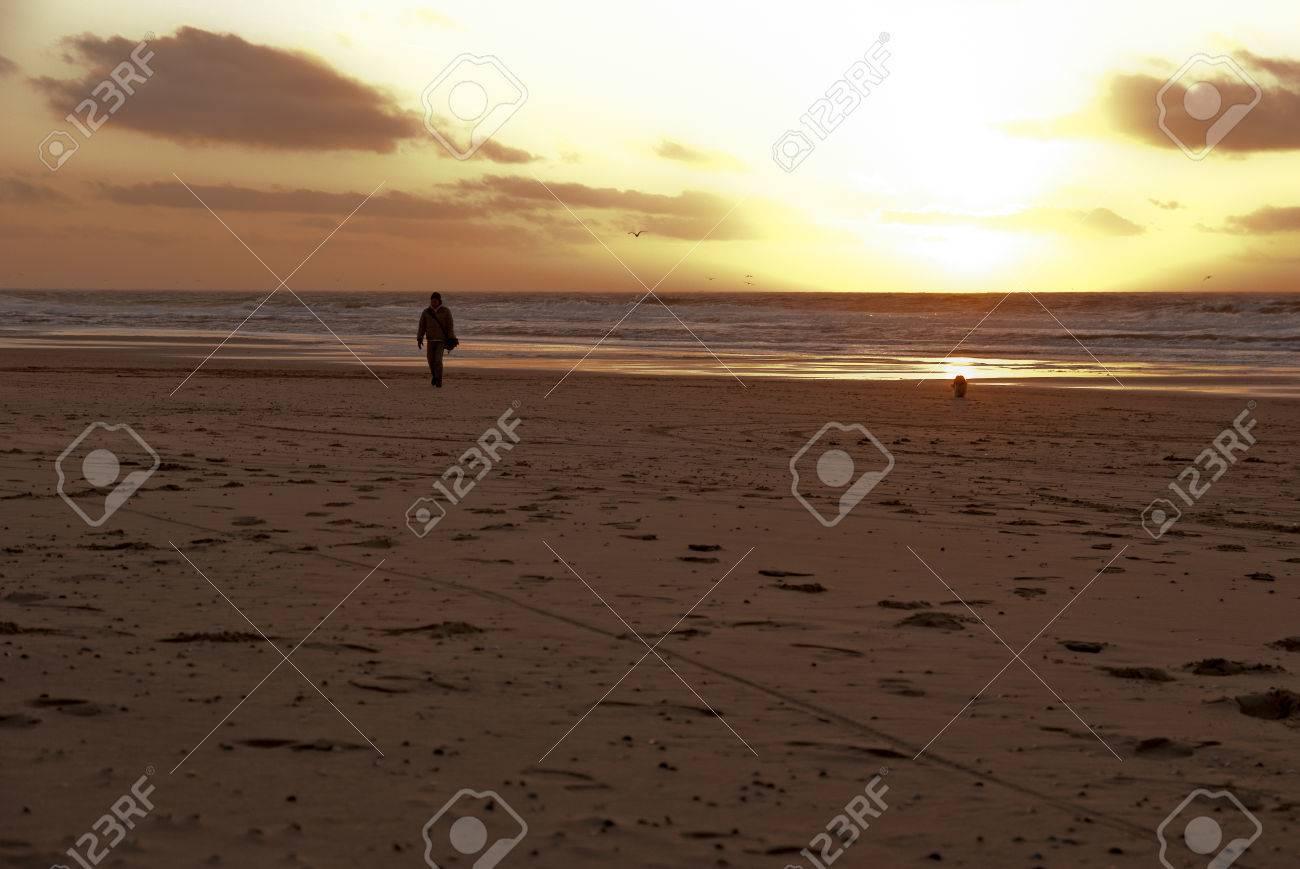 Strand nordsee sonnenuntergang  Mensch Und Hund Zu Fuß Am Strand Bei Sonnenuntergang über Der ...