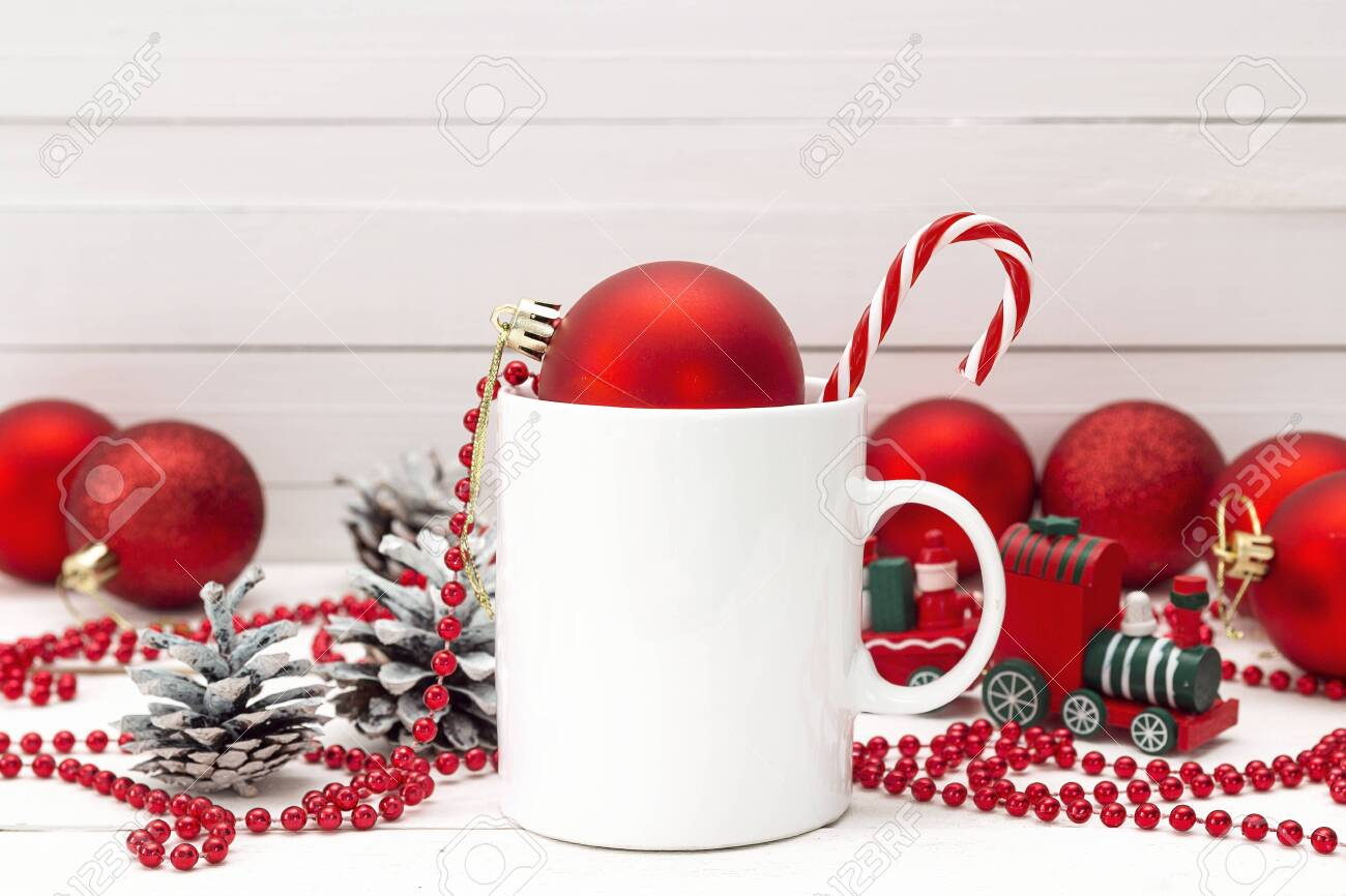 White coffee mug with candy cane and Christmas decorations on