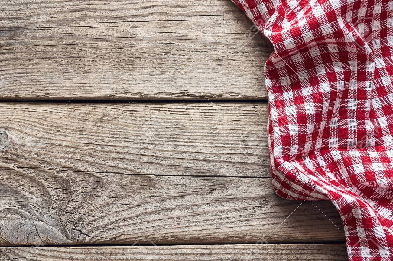 Red checkered napkin on an old wooden table. Space for text, top view. - 141434944