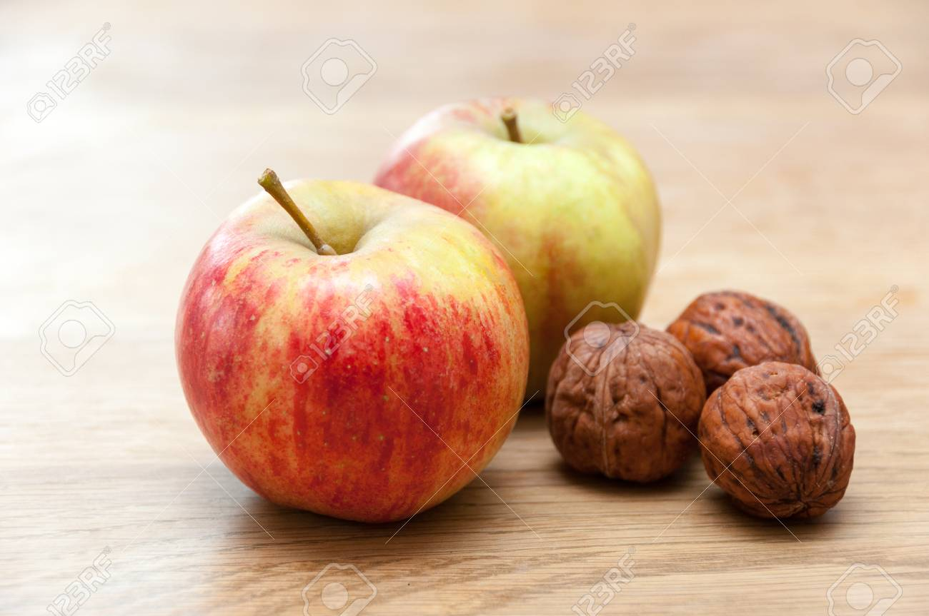 26f4589feb08 Nuts and apples on wooden table Stock Photo - 48286048
