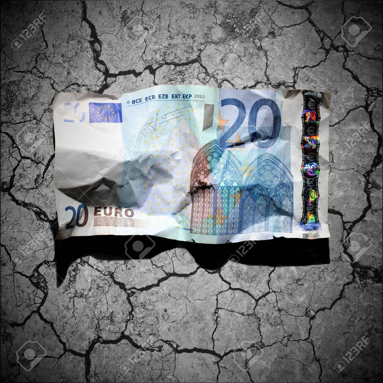 Financial crisis concept - crumpled 20 euro banknote on dry soil background - 12748595