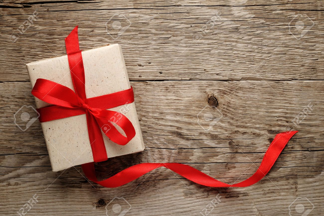 Gift box with red bow on wood background - 13978780
