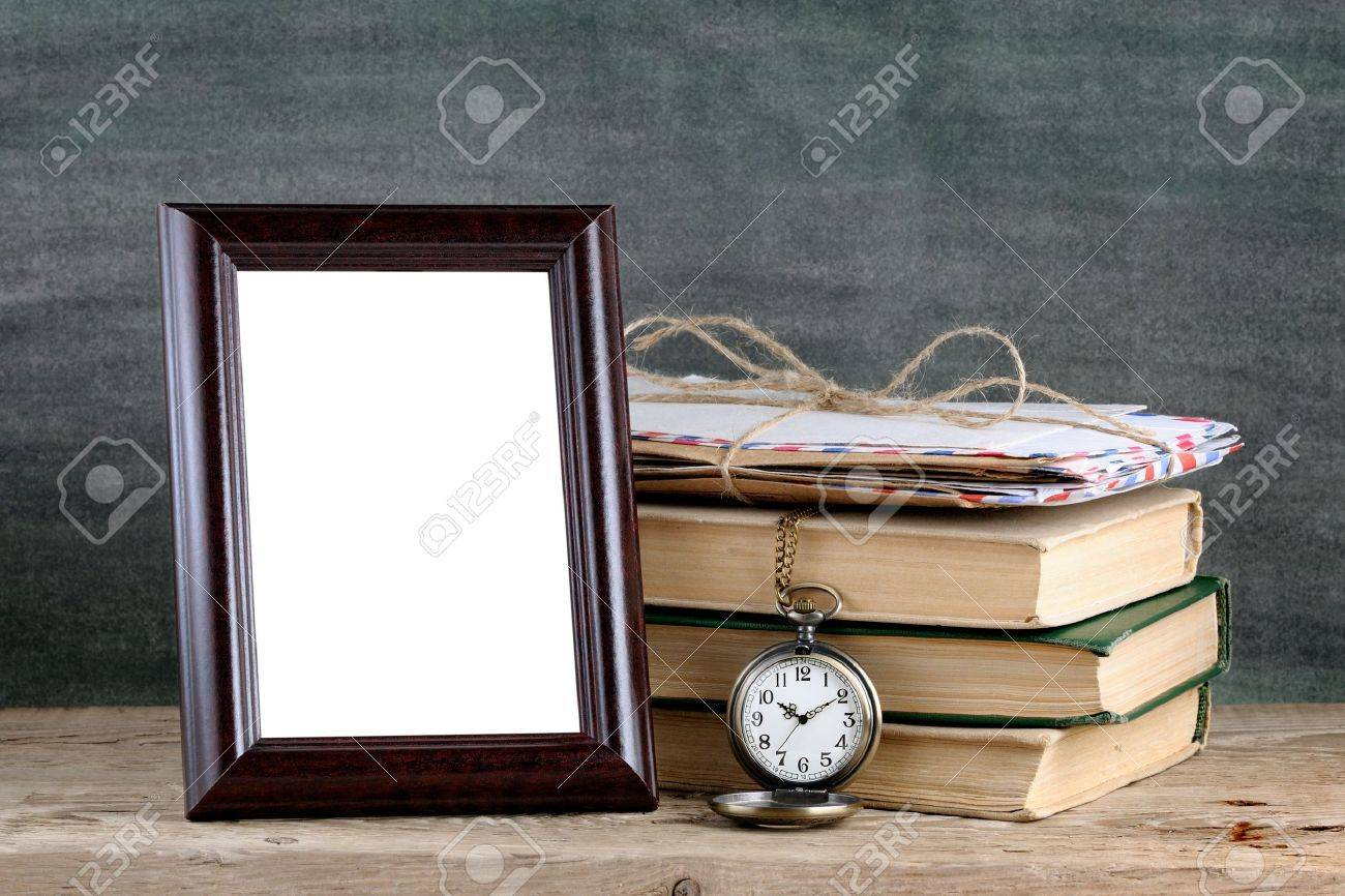Photo frame and pile of old books on wooden table - 18001364
