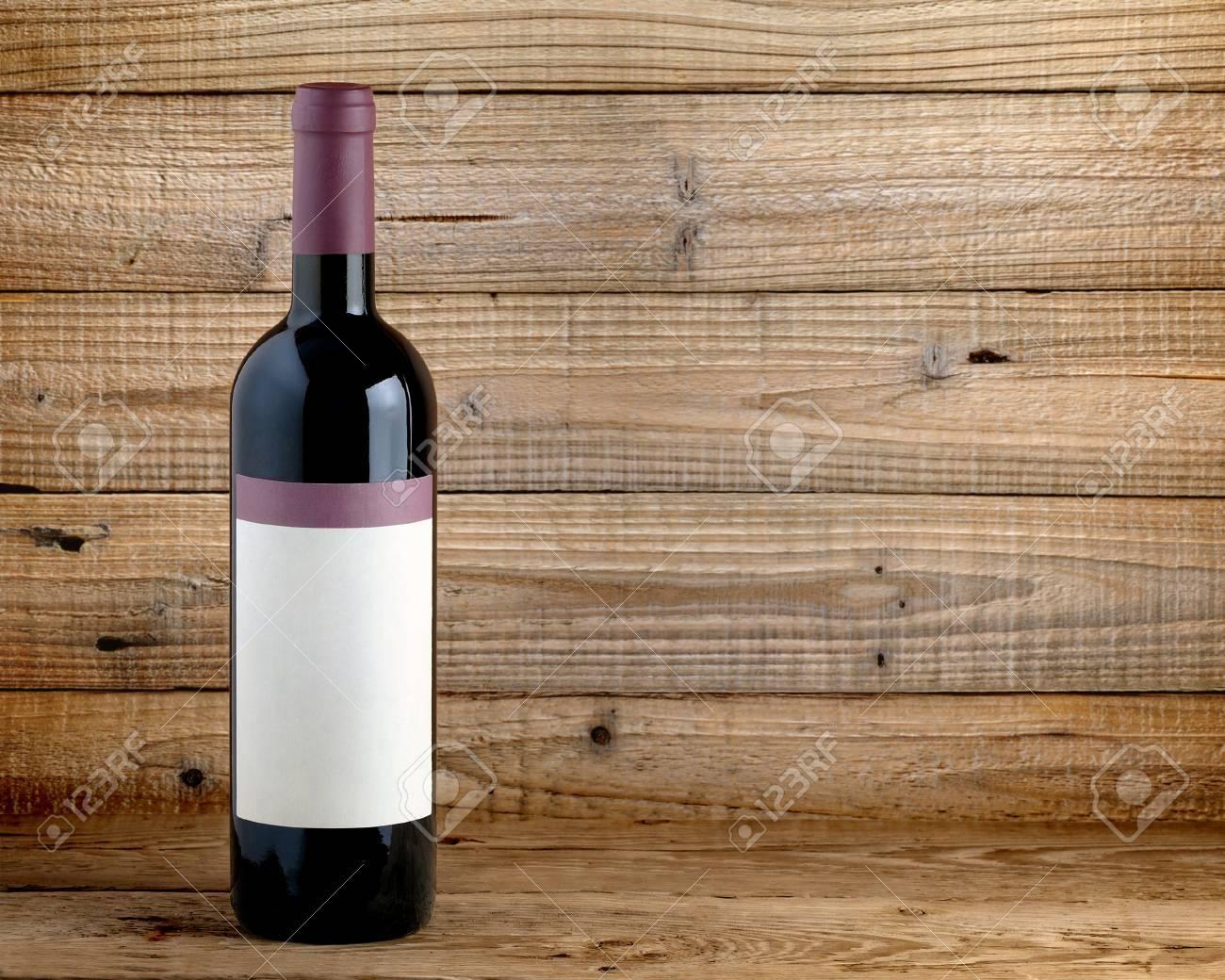 Wine bottle on wooden table - 26078009