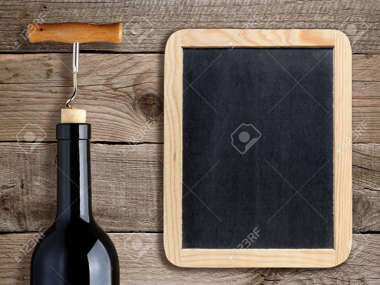 Bottle of wine and blank blackboard on wooden background - 35154624