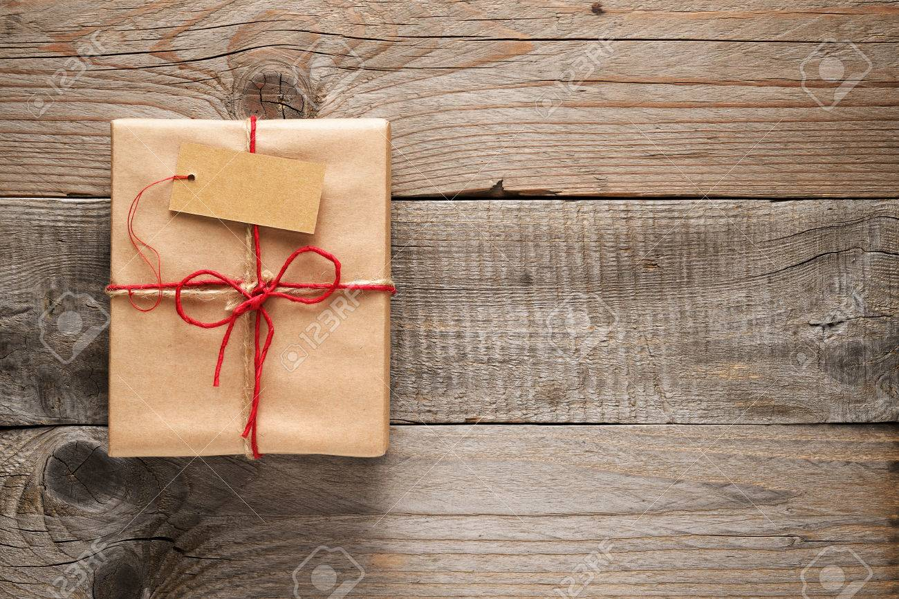 Gift box with tag on wooden background - 38912514