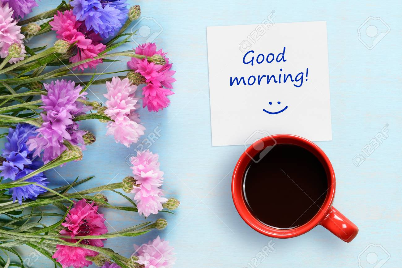 good morning wishes coffee cup and cornflowers on blue background